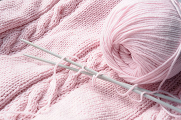 Clew and needles on pink knitted pattern.