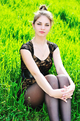 elegant girl sitting in grass