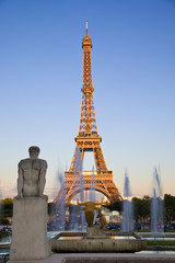 Eiffel tower at sunset, behind Trocadero fountains and statues