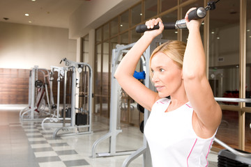 A side view of a woman exercising on a cable cross machine