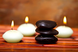 Spa stones and candles on bamboo
