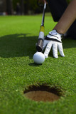 Aiming a golf ball to a hole on a putting green