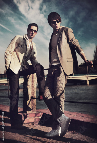 Two handsome friends posing on a city promenade
