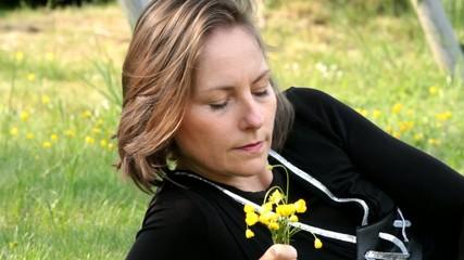 femme composant son bouquet de boutons d'or