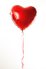 Red heart ballon with red and white strings on white fond