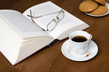 Cup of coffee, old book,  glasses & biscuits, soft focus