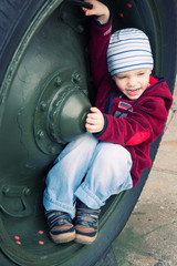 The little boy sitting in a military vehicle wheel