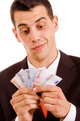 Happy young business man with money, over white background