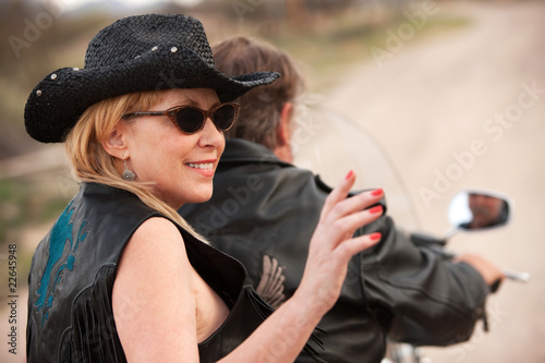 Fun couple riding motorcycle outside in the desert