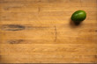A lime sits on a worn butcher block cutting board