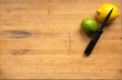 A knife with lemon and lime on cutting board