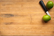 Limes and a knife sit on a worn butcher block cutting board
