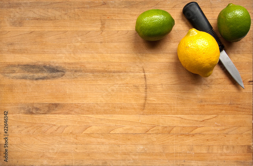 A lemon and limes on a worn butcher block cutting board