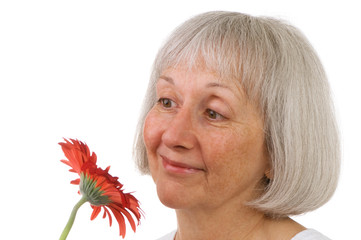 Senior Lady Enjoys A Red Daisy Flower