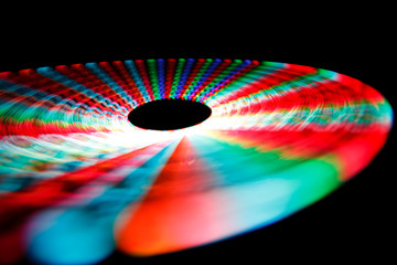 Colorful glowing trail rotating LED, in form of disc on black