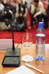 conference in hall. bottle, microphone, glass and pen on table.