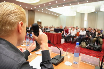 conference in hall. man with microphone. focus on hand