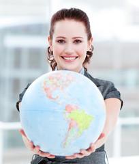 Charismatic businesswoman holding a terrestrial globe