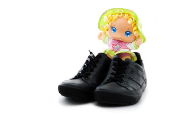 large-headed doll with feet booted in adult gumshoes