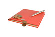 red notebook and steel pen with coins