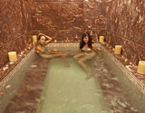 Two young girls in a jacuzzi at a spa poster
