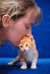 The girl kisses a red kitten