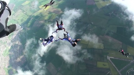 Five skydivers in freefall falling through clouds