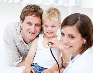 Portrait of beautiful female doctor examining a little boy with
