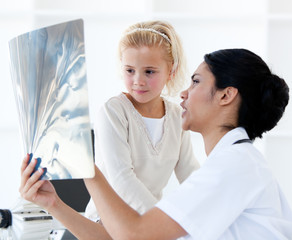 Confident female doctor showing an x-ray to a little girl