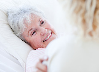 Cheerful senior woman lying on a hospital bed talking with her g