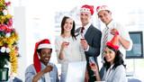 Mosolygó üzleti csapat pezsgőt iszik, hogy ünneplik a karácsonyt