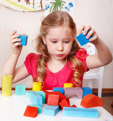 Child with wood block  in play room.