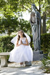 Beautiful child wearing white dress sitting on park bench