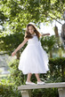 Beautiful child wearing white dress playing on park bench