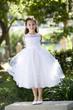 Beautiful child wearing white dress standing on park bench