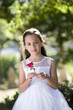 Beautiful child wearing white dress in park holding flower