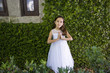 Beautiful child in white dress by ivy-covered wall