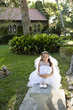 Beautiful young girl in white dress sitting on bench