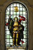 Historic stained glass of knight holding sword aloft