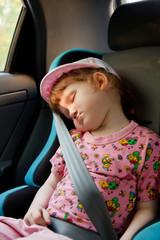 Cute little girl sleeping in a car