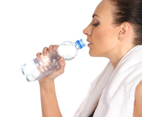 A young and sporty female is drinking fresh water after training