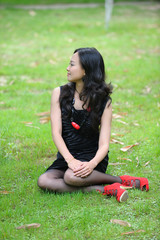 asian woman sitting on grass