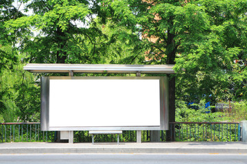 a bus stop with a blank billboard for your advertising .
