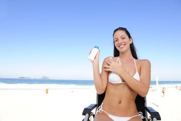 woman in wheelchair applying sunscreen on the  beach
