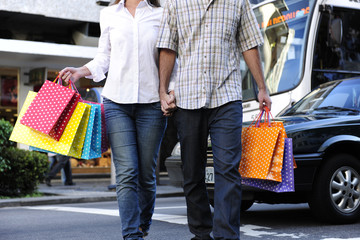 couple with shopping bags crossing the street