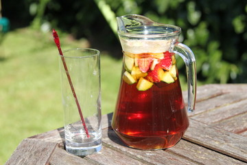 jug of Pimms and lemonade cocktail with fruit and empty glass
