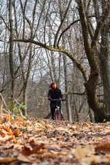 Young female bicycle rider in autumn park