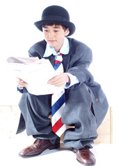 boy in business suit reading a newspaper isolated on white