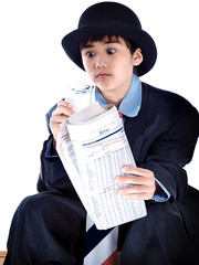 boy in a suit reading the financial news during breakfast