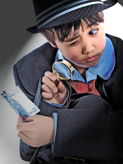 boy in a suit holding euro banknote under a magnifying glass